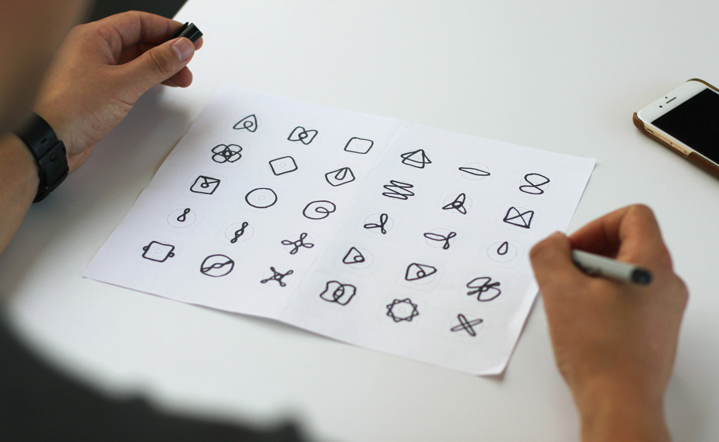 A piece of paper on a table showing doodles of various icons