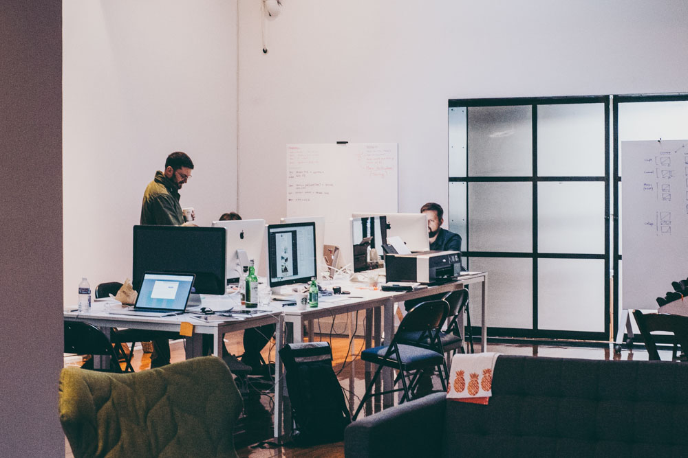 Photo of an open office setting with two employees at their desks