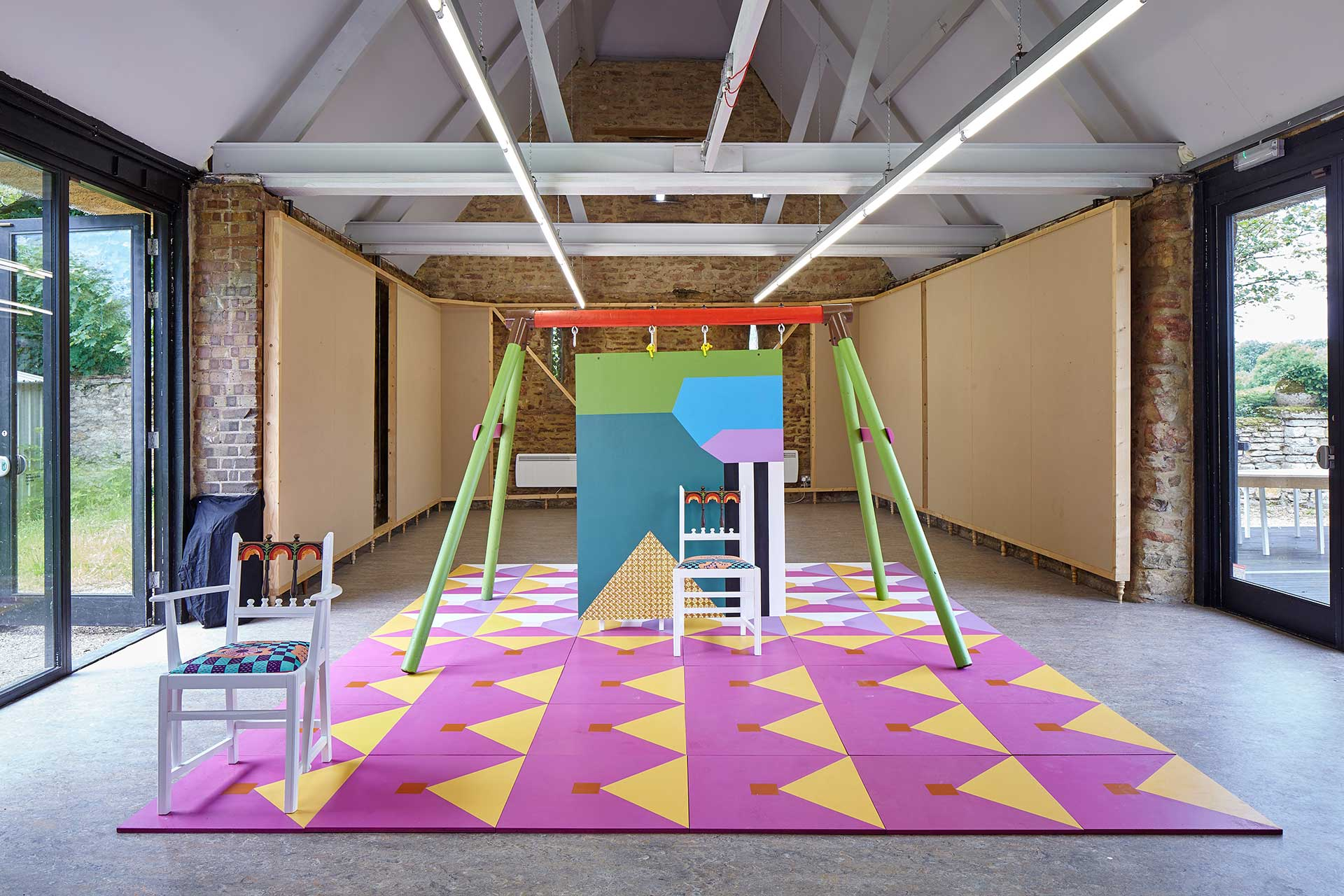 A studio space with a brightly colored rug, backdrop, and two chairs.