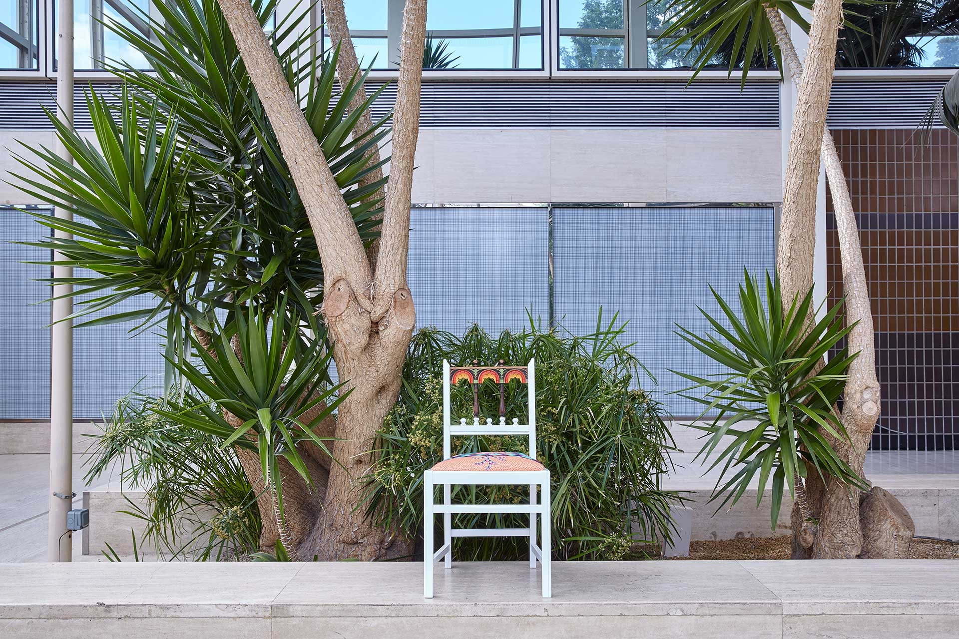 A chair sitting on a curb under some palm trees.