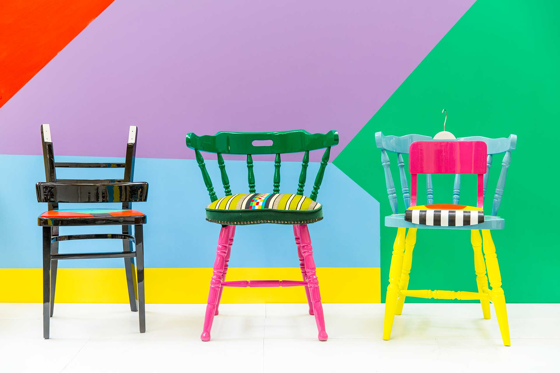 Three brightly colored chairs lined up in front of a multi-colored wall.