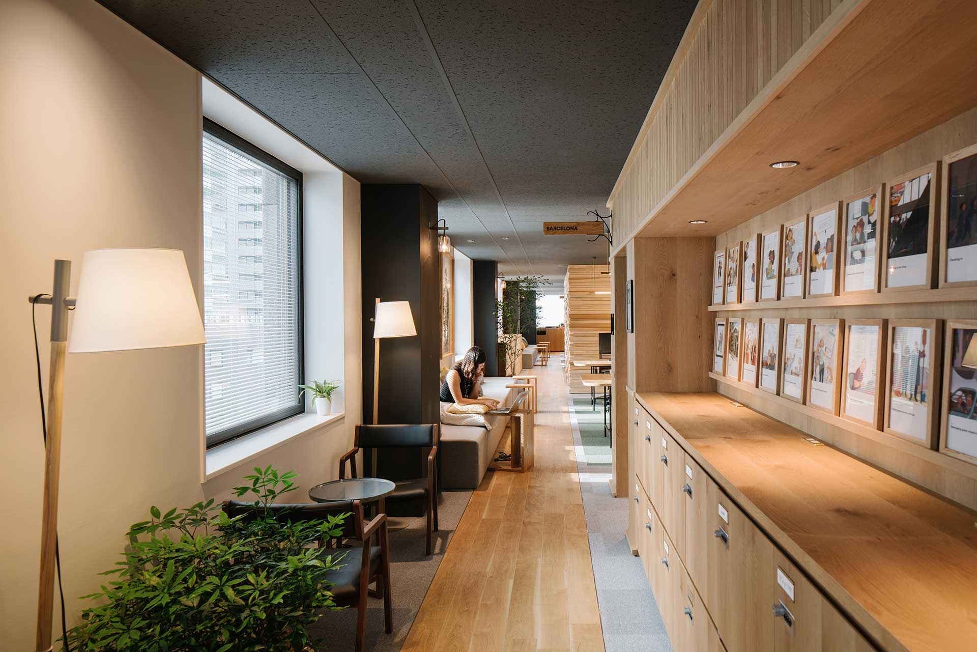 A narrow, well lit hallway with plants and light wood filing cabinets lining the walls.