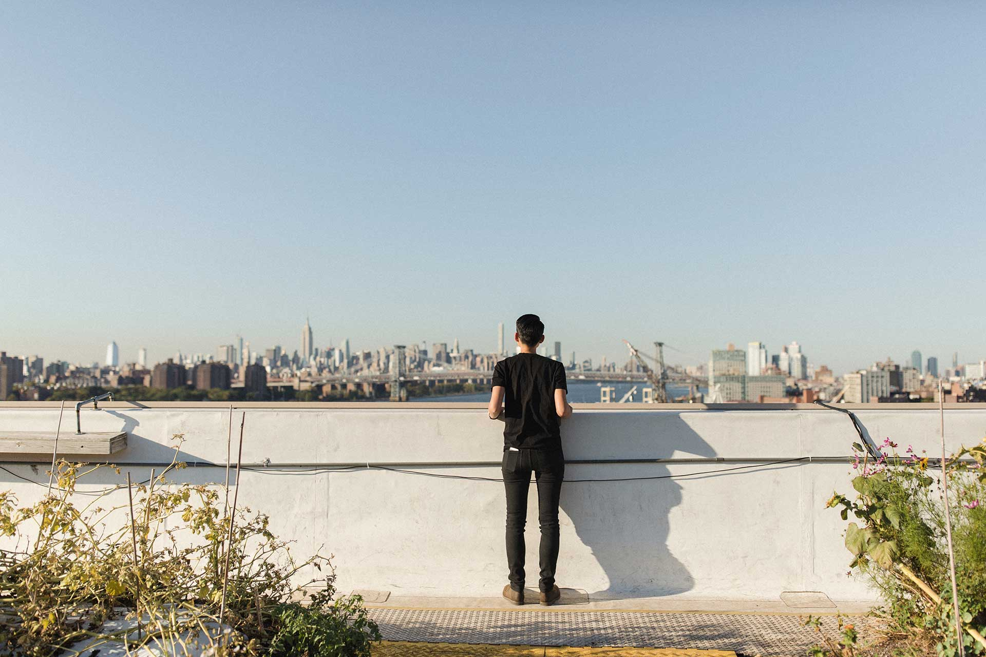 A man stands on the rooftop looking out at the city skyline.