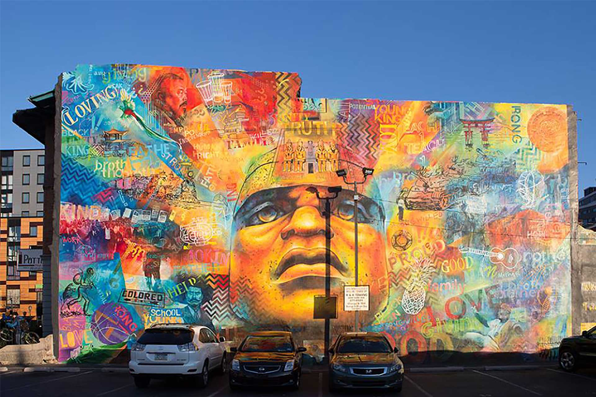 A colorful mural on the side of a parking lot.