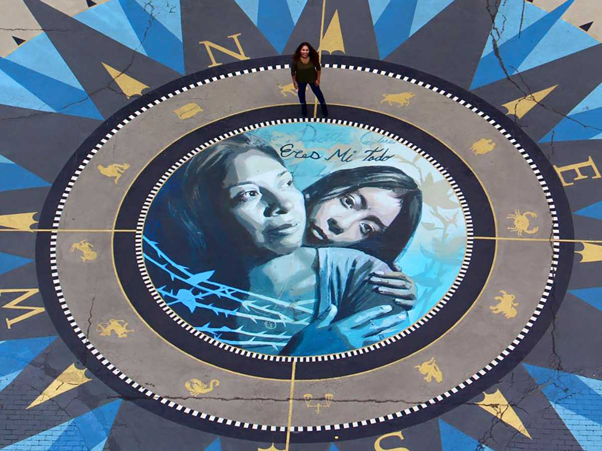 Michelle Angela Ortiz stands on a painted mural, a large compass with two women embracing in the center.