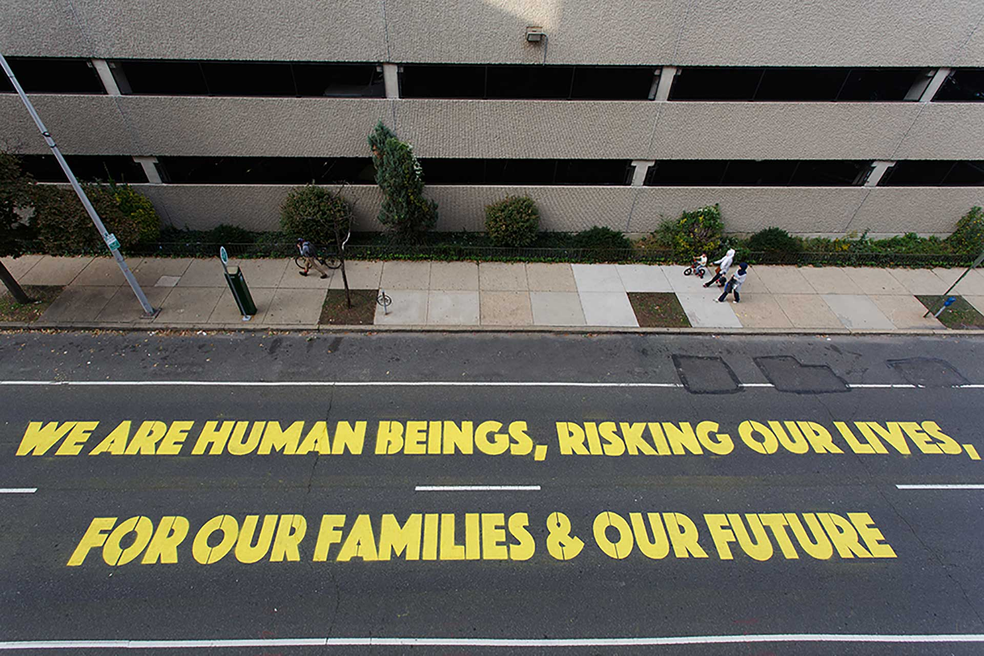"An overhead shot of a city street on which the words ""We are human beings, risking our lives for our families and futures"" has been painted."
