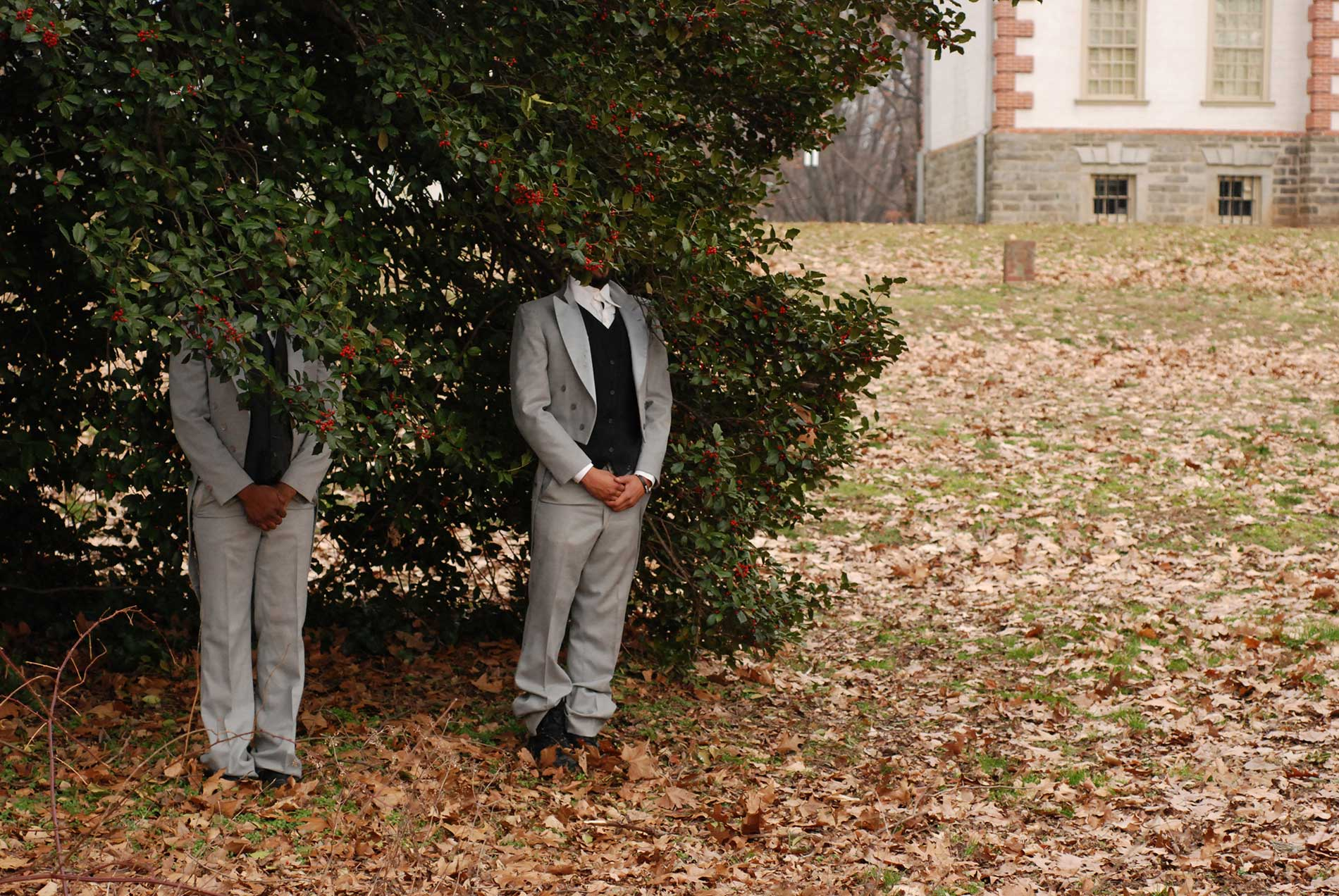 Two men in suits stand with their heads covered in a large hedge.