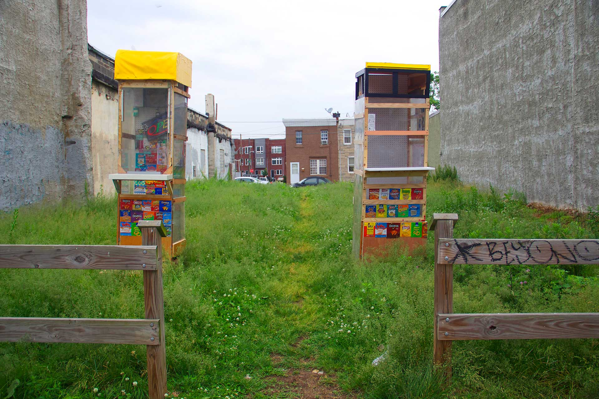 Two wooden, handmade ticket booths stand in a grassy lot.