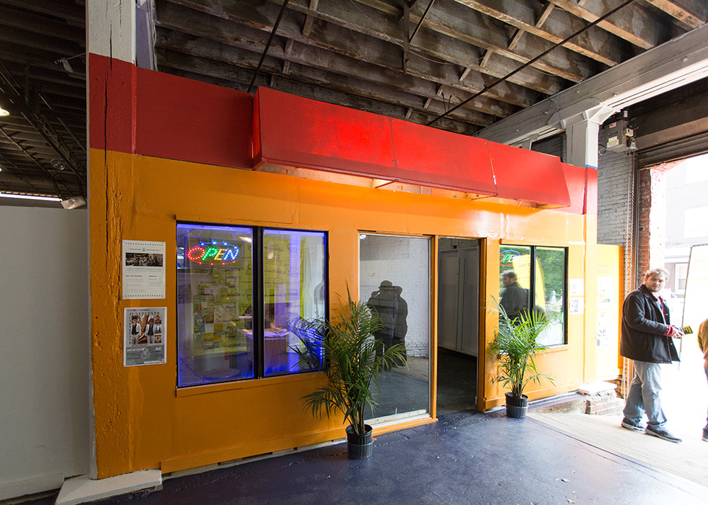 A recreation of the exterior of a fast food restaurant, installed in a warehouse.