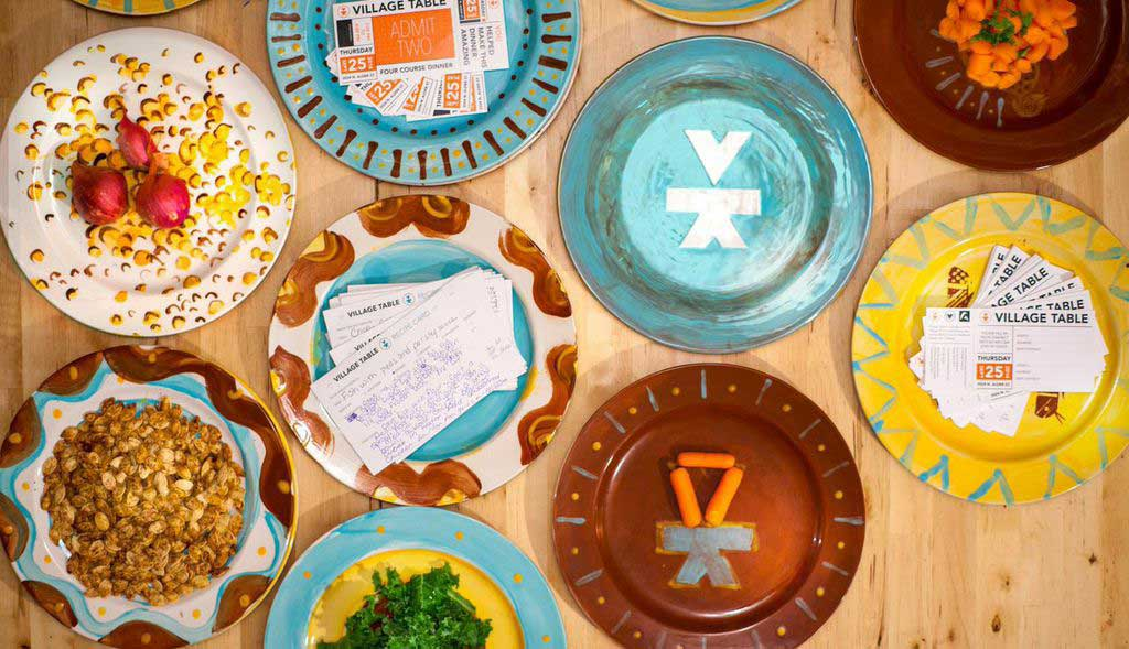 Overhead shot of colorfully painted plates, some with food on them.