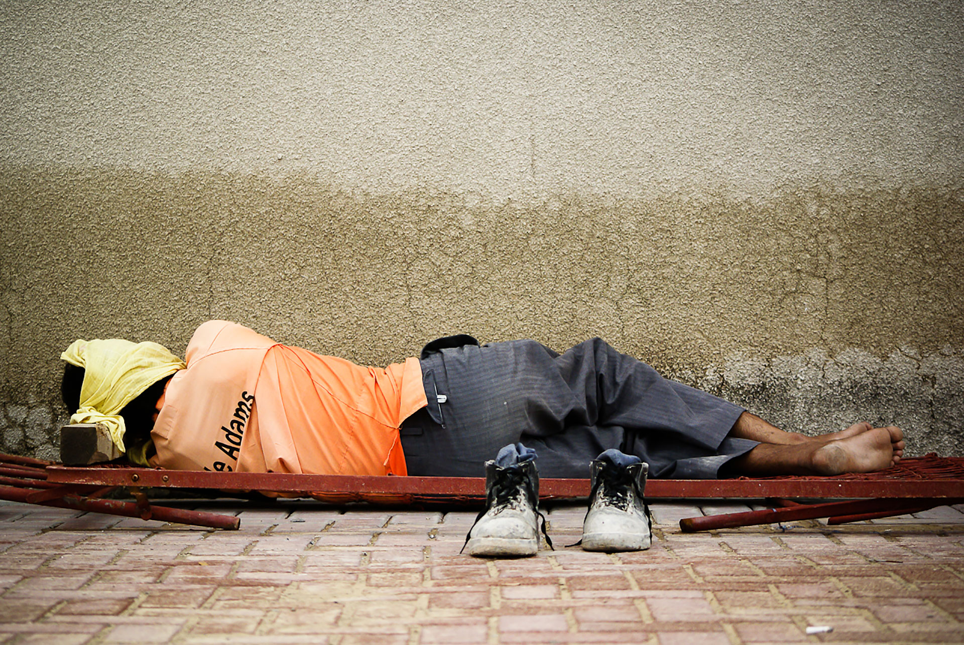An Indian construction worker asleep on a brick street.