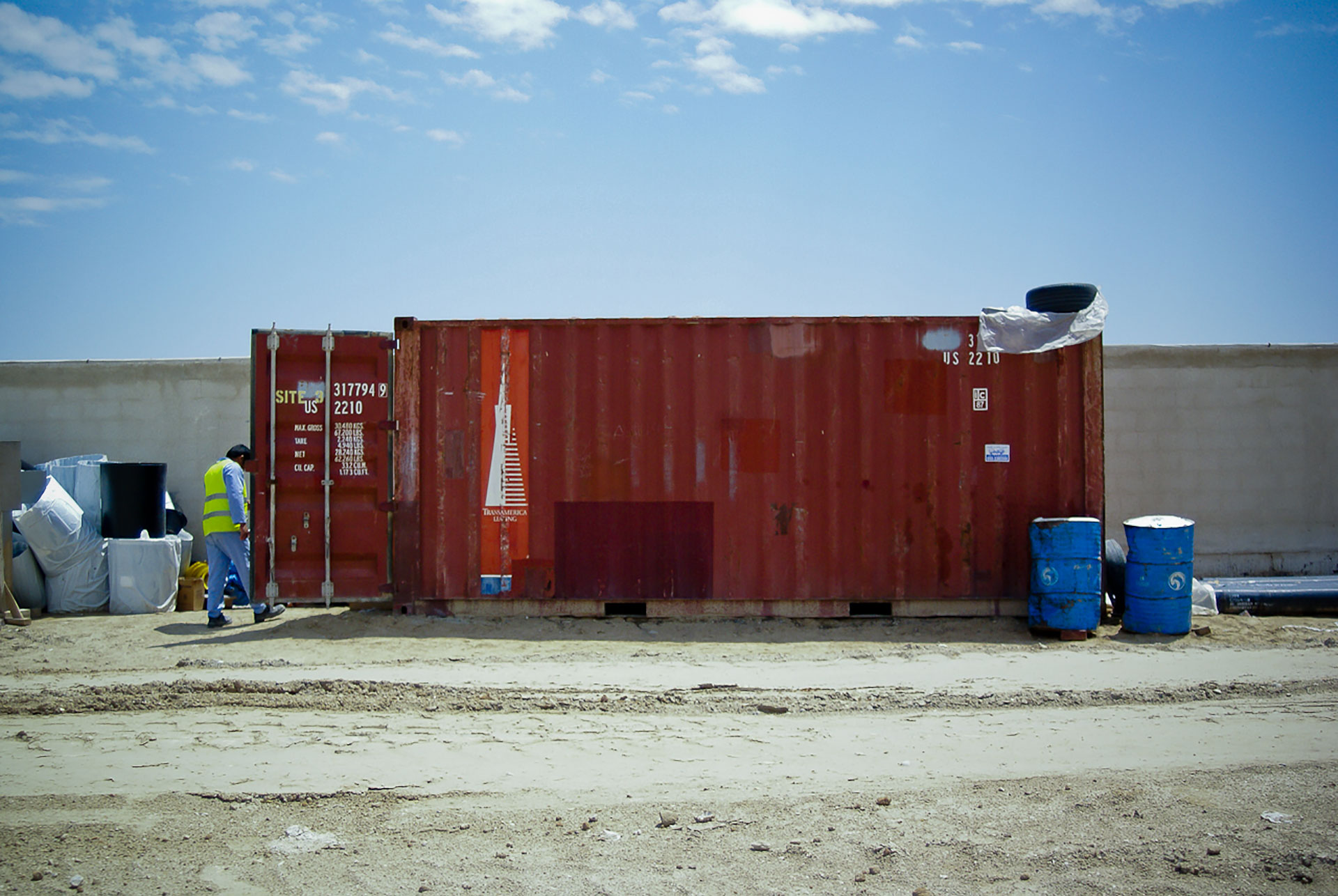 A construction worker next to a red shipping container.