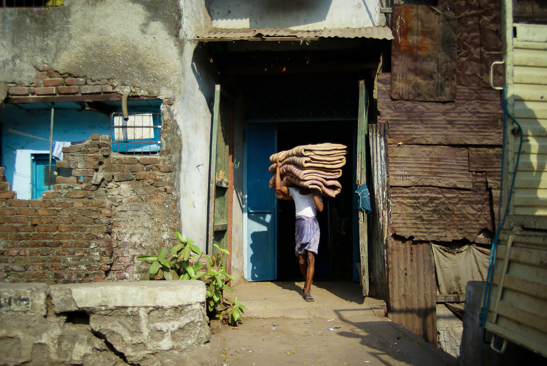 A young man carrying blankets on his head in Dharavi, India.