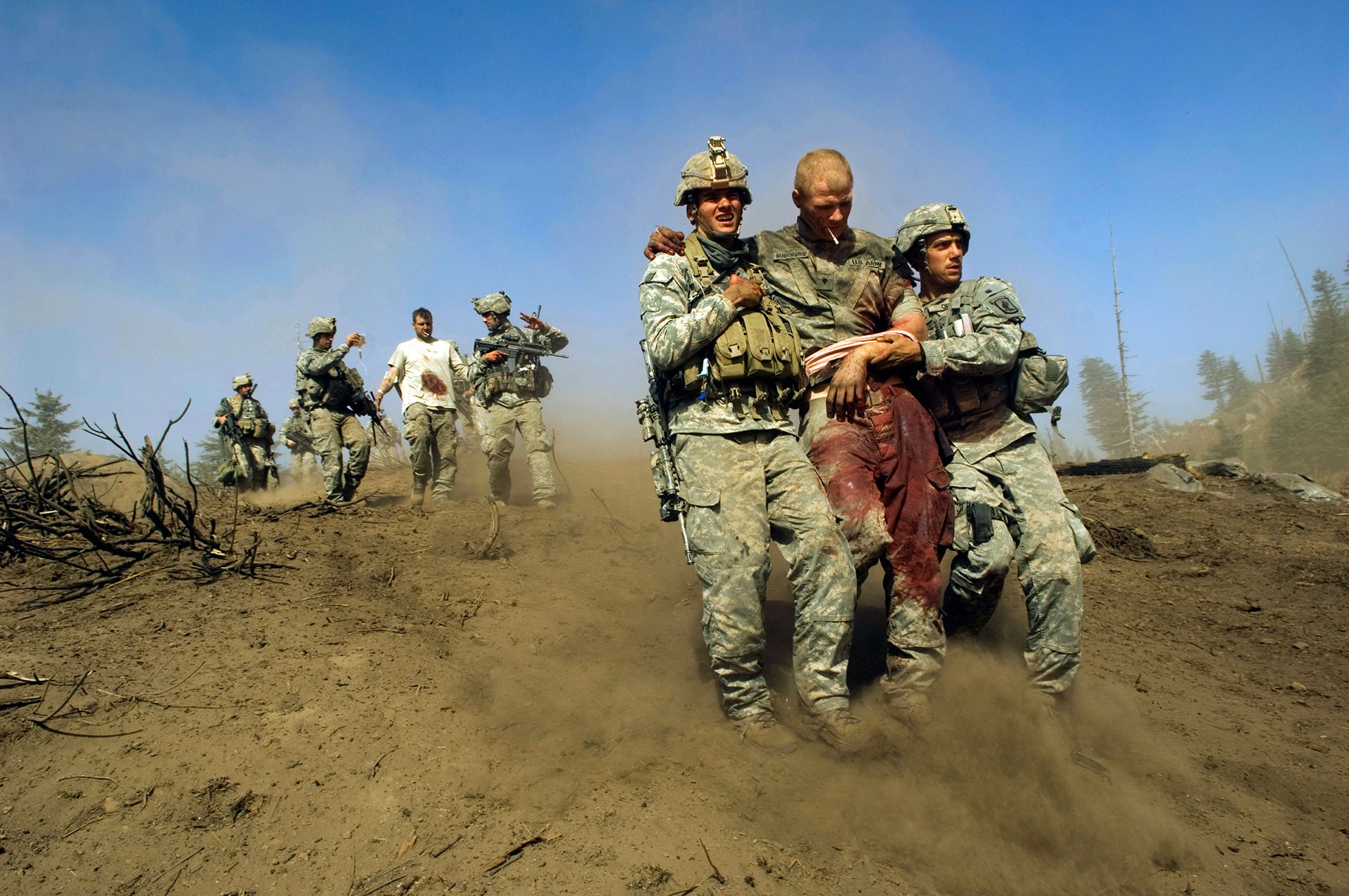 KORENGAL VALLEY, AFGHANISTAN. Specialist Carl Vandeberge, center, and Sargeant Kevin Rice, behind, are assisted as they walk to a medevac helicopter minutes after they were both shot in the stomach during a Taliban ambush, which killed one soldier, and wounded both of them. Spc. Carl Vandeberge and Sgt. Kevin Rice, were flown out immediately for surgery. October 23, 2007.