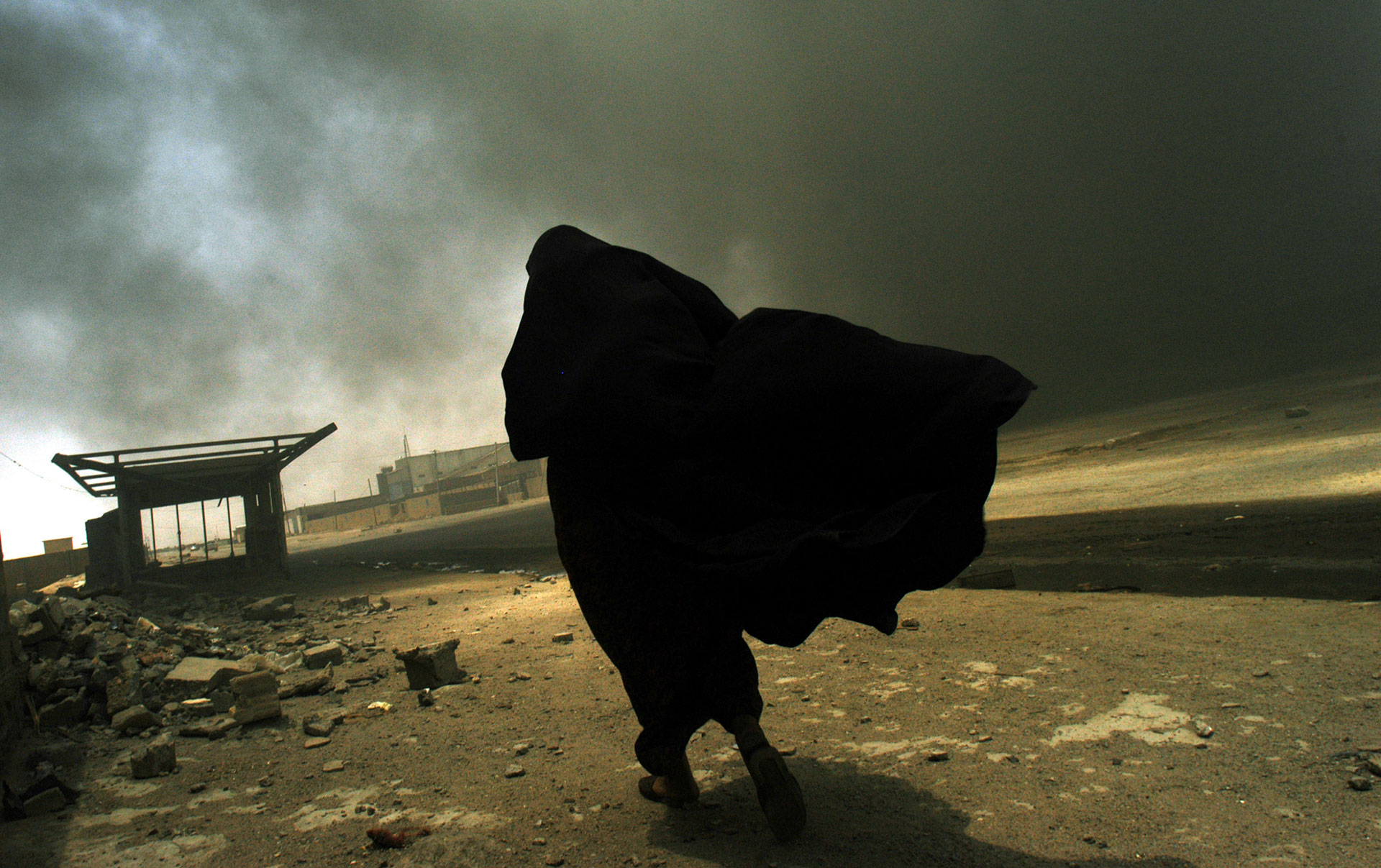 A woman in a burqa walks towards a smoking building.