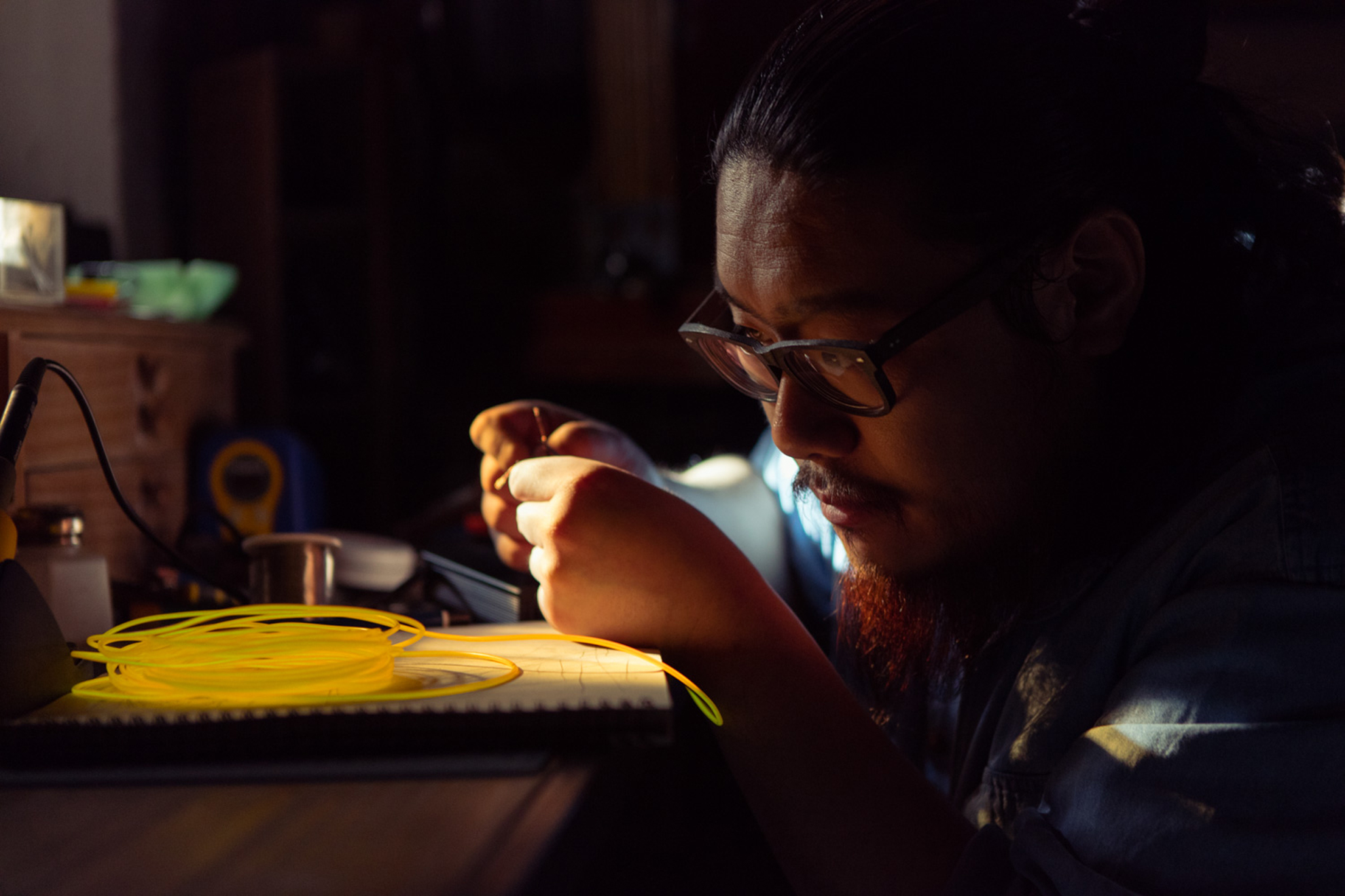 An artist from the video works with neon string.