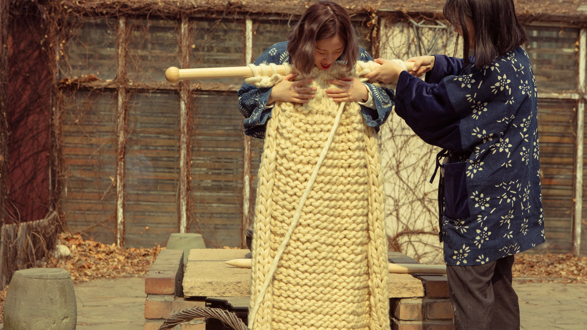 An artist from the video and young girl pose with an oversized knitting needle and scarf.