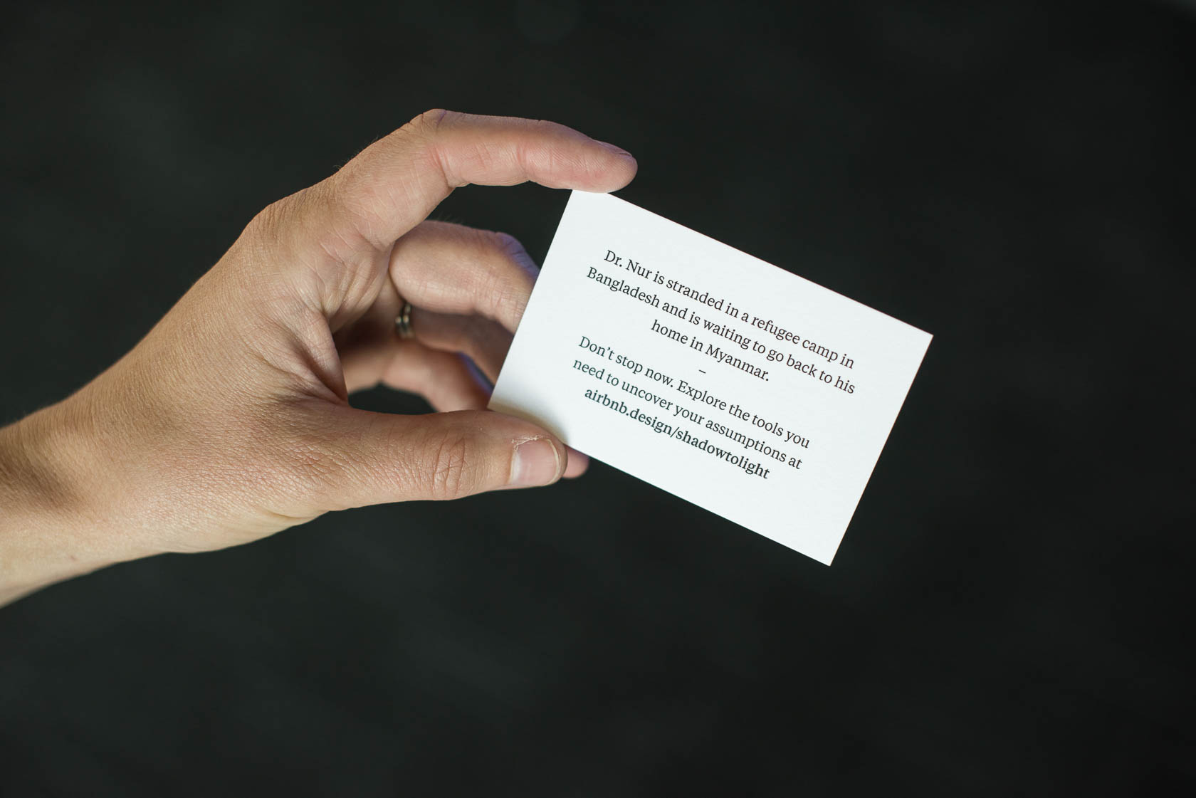A hand holding a business card, which shares the story of a refugee and a link to airbnb.design/shadowtolight.