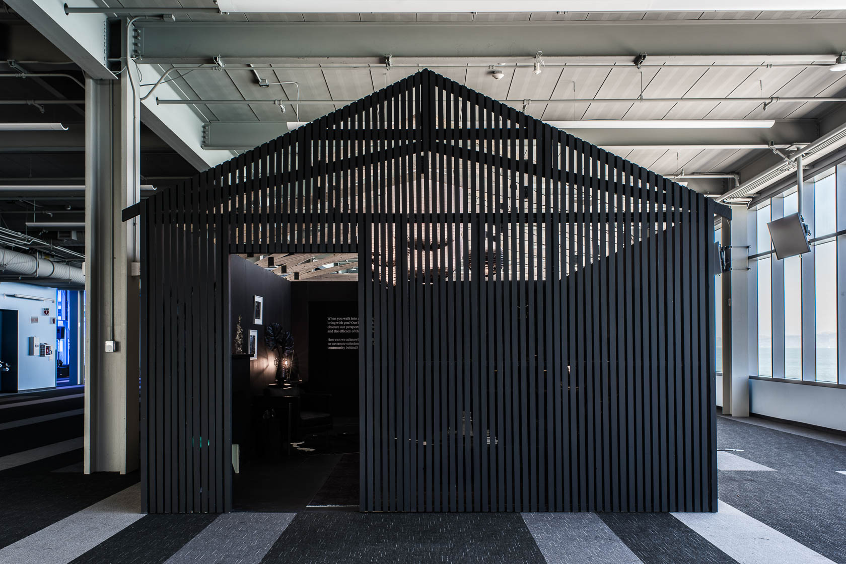 A home-like structure made of black slats, standing in an event space.