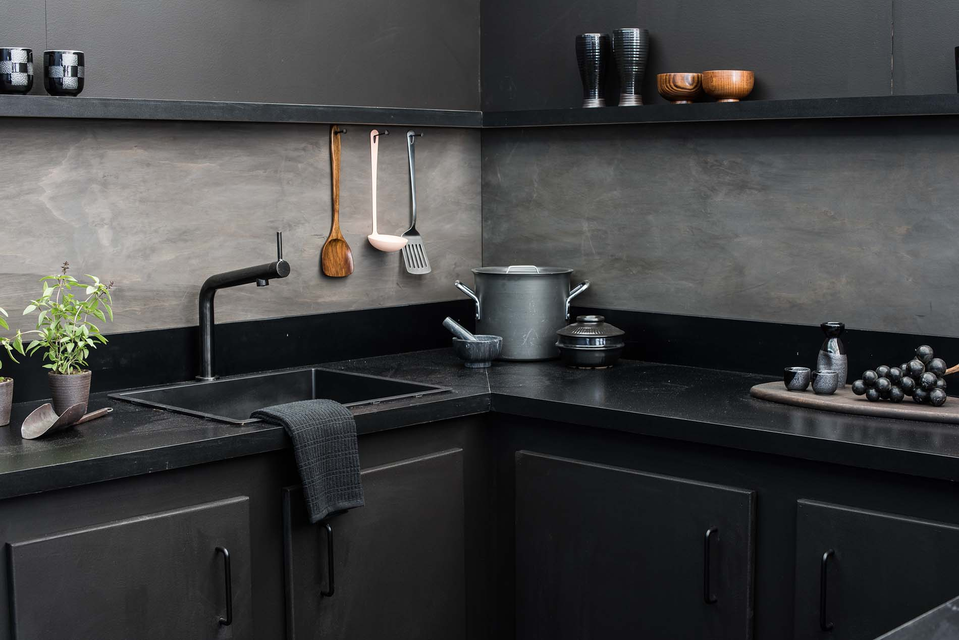 A light pink-colored ladle hanging in an all black and gray toned kitchen.