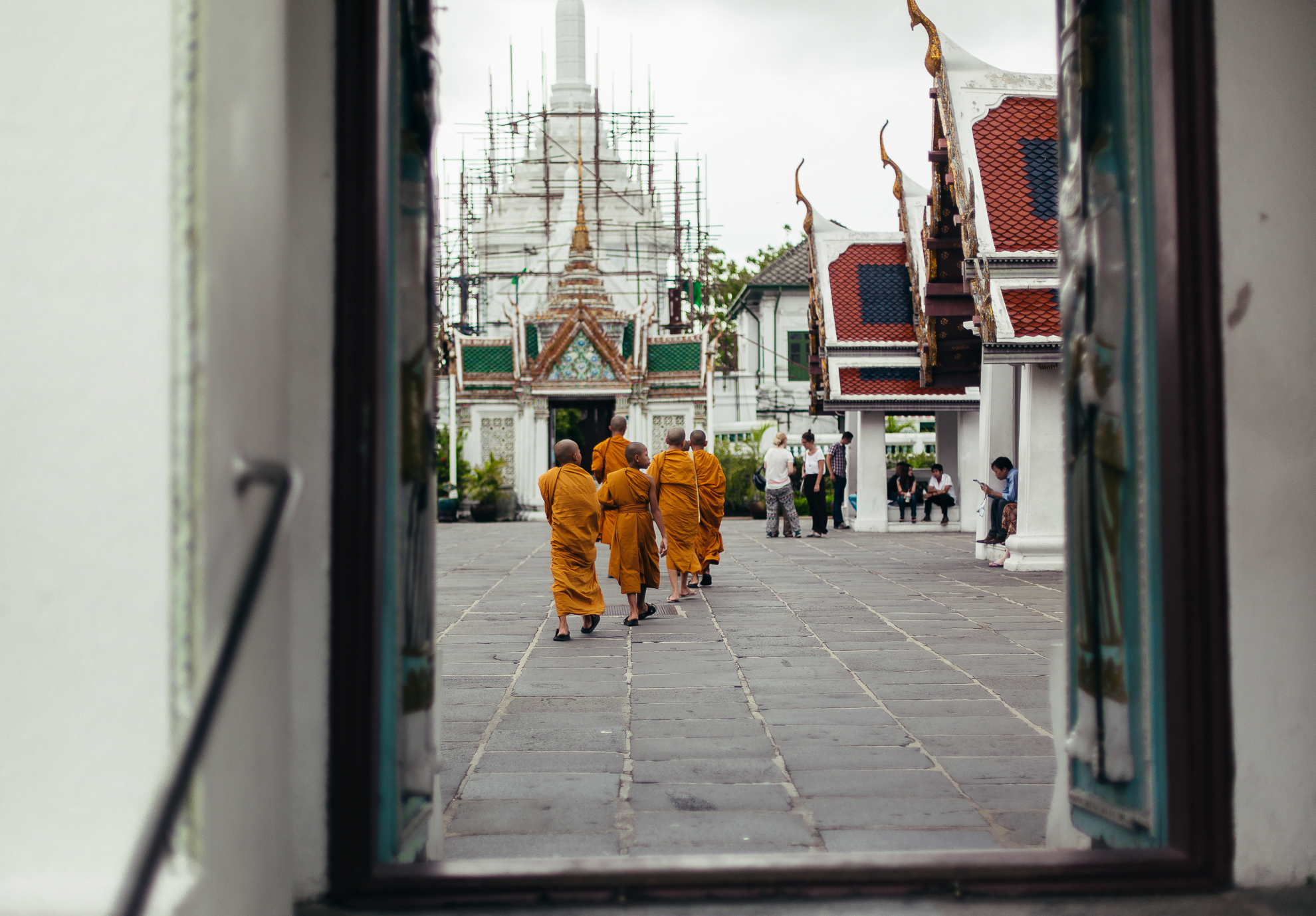 A photo of monks walking away from behind