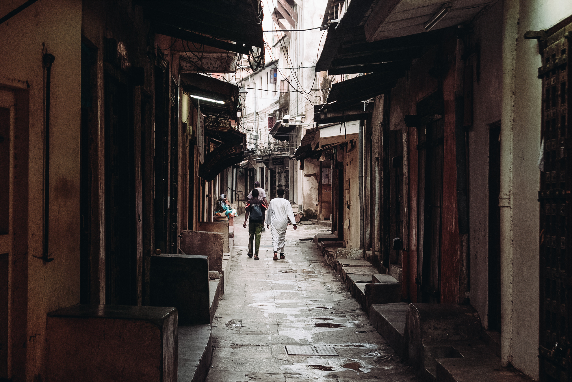 People walking down an alley, away from the camera