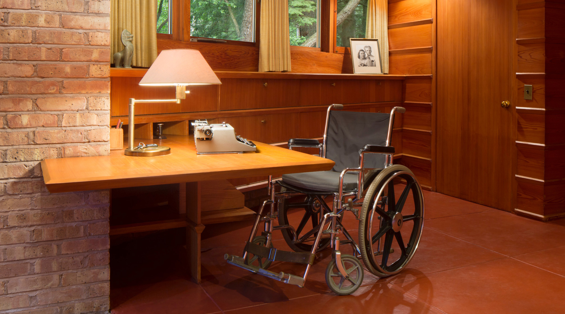 A custom-designed writing desk with clearance for a wheelchair and a framed portrait of the homeowners on a shelf nearby.