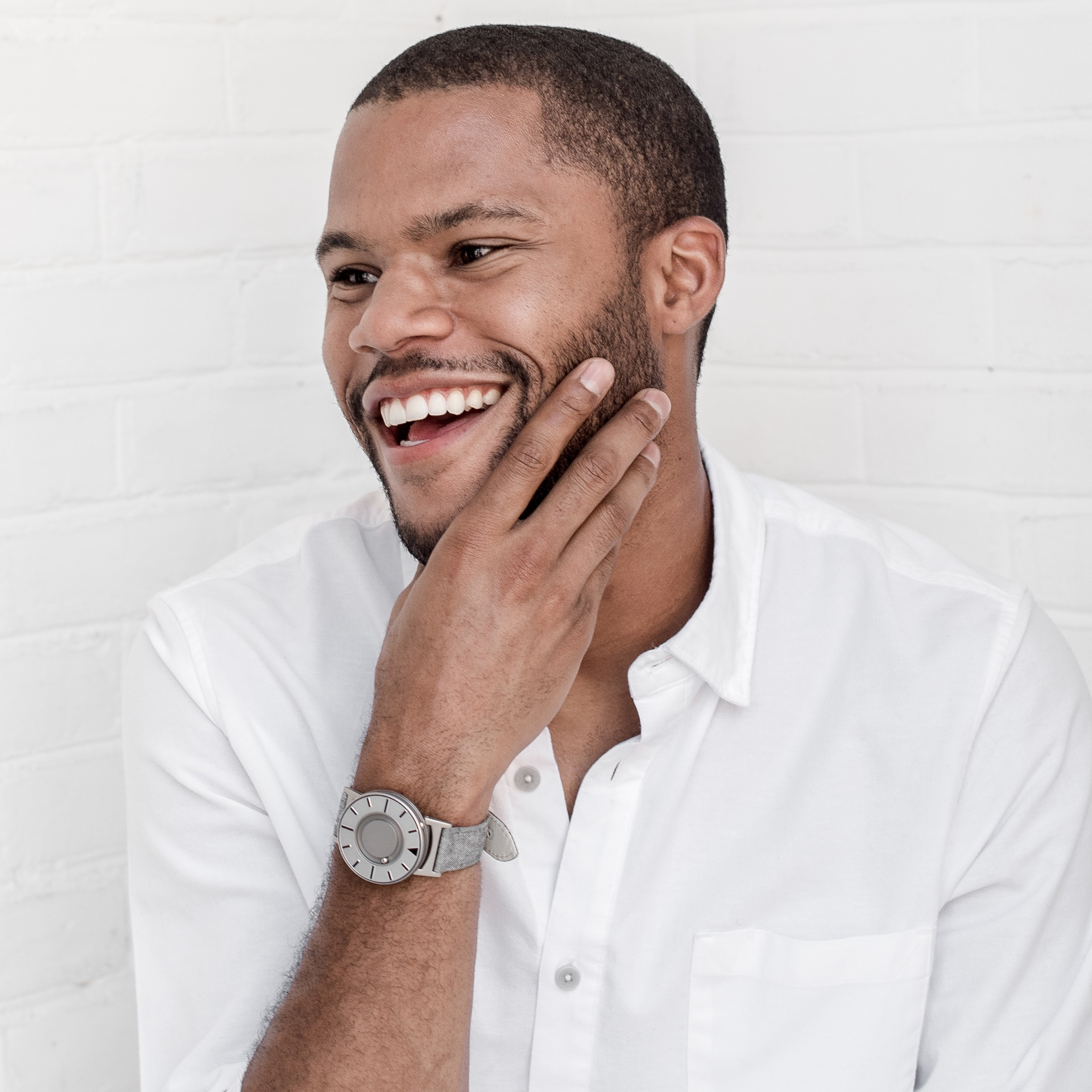 A smiling person wearing a white collared shirt and a silver Eone watch against a white brick wall.
