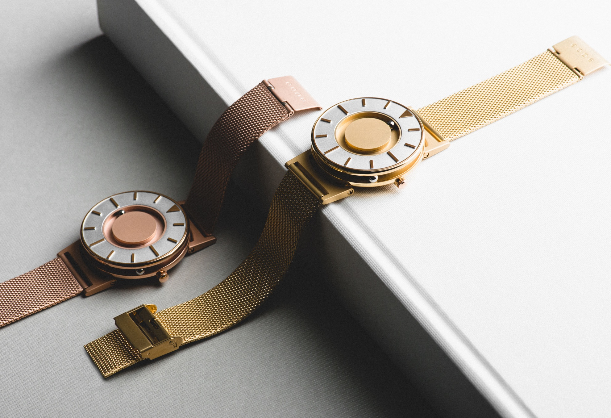 Two models of the Eone watch are draped across a book, one is metallic gold and the other is rose gold.